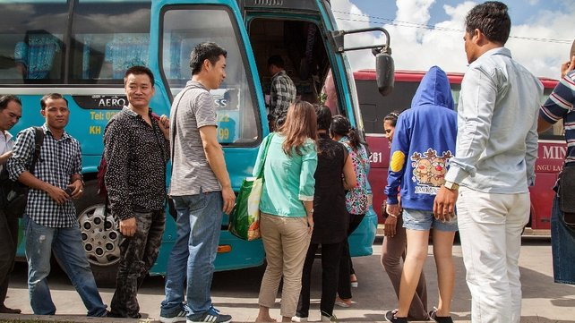 A group of Chinese nationals wait to board a bus to the Cambodian capital Phnom Penh after fleeing Vietnam