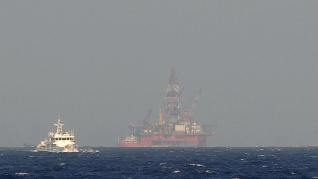 A Chinese coast guard vessel (L) sails near China's oil drilling rig in disputed waters in the South China Sea