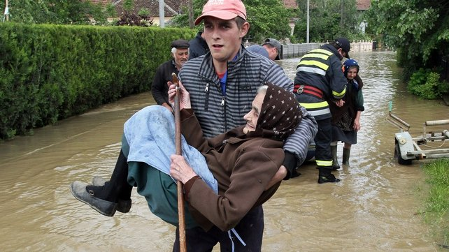 A man carries an elderly woman out of her flooded house in the village of Obrez, south of Belgrade