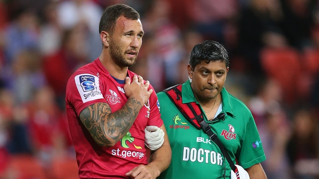 Quade Cooper leaves the field at Suncorp Stadium clutching his injured shoulder