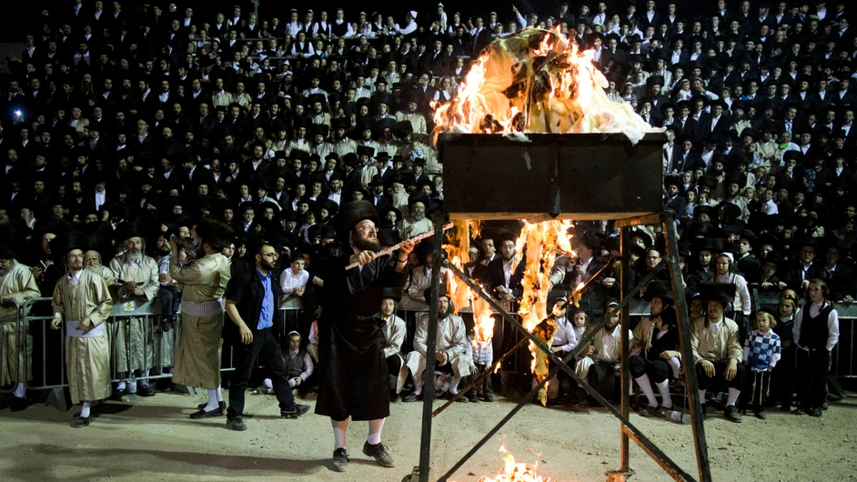 A man lights a bonfire in the neighborhood of Mea Shearim in Jerusalem, Israel during the commemoration the holy day of Lag Ba'Omer