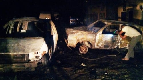 A man checks the wreckage of a car at the scene of the blast