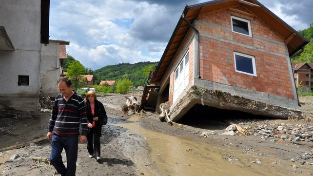 People pass by damaged houses after flooding in Serbia
