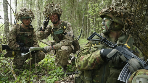 A member of the Estonian Scouts Battalion looks on as British soldiers plan their movements during the NATO 'Spring Storm' military exercises in a forest near Sengaste, Estonia