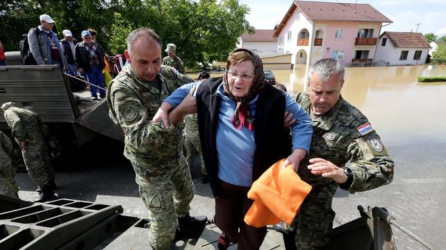 Rescue workers help to evacuate an elderly woman in a flooded street in the village of Gunja, in eastern Croatia