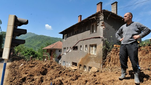A man observes as workers clear earth from a landslide in the flooded village of Nemila in central Bosnia