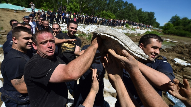 Volunteers and police officers pass sandbags to reinforce the bank of the river Sava near Sabac, 100 kilometres west of Belgrade