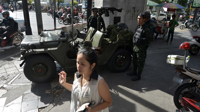 A woman passes by soldiers as they secure Ratchaprasong intersection in Bangkok