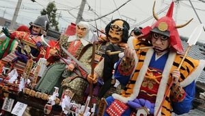 Festival goers carry huge paper dolls of historical Japanese figures during the Mikuini annual festival in Sakai, Japan