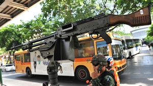 A gun mounted on an army vehicle as soldiers stand guard on a busy city centre street after martial law was declared in Bangkok, Thailand