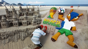 A man paints a 2014 World Cup design on a sand castle on Copacabana Beach as Brazil prepares to host the tournament