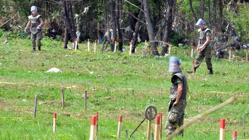 Mine clearance experts search a field after flood waters receded from the village of Cekrekcije, near Sarajevo