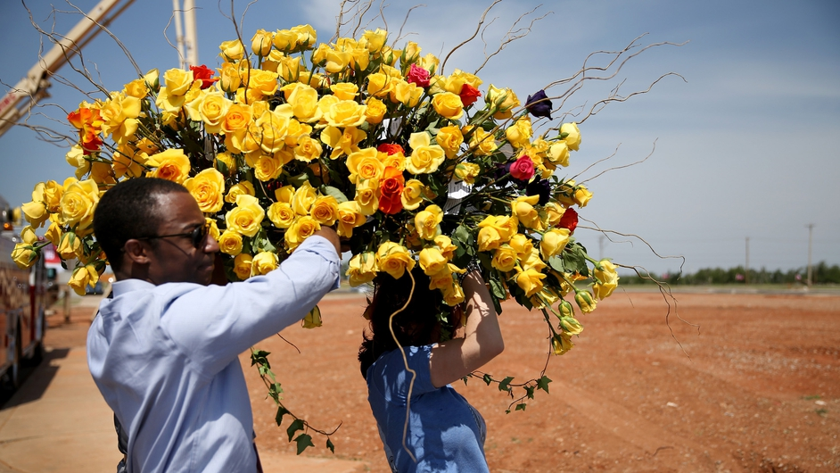 Armand McCoy and Jennifer Halstead carry a bouquet of flowers during a remembrance ceremony for victims of last year's Oklahoma tornado