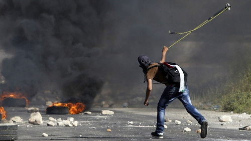 A masked Palestinian demonstrator uses a slingshot during clashes with members of the Israeli security forces outside the Israeli-run Ofer prison in the West Bank village of Betunia, on 16 May, the day after two Palestinian youths were shot dead by Israel