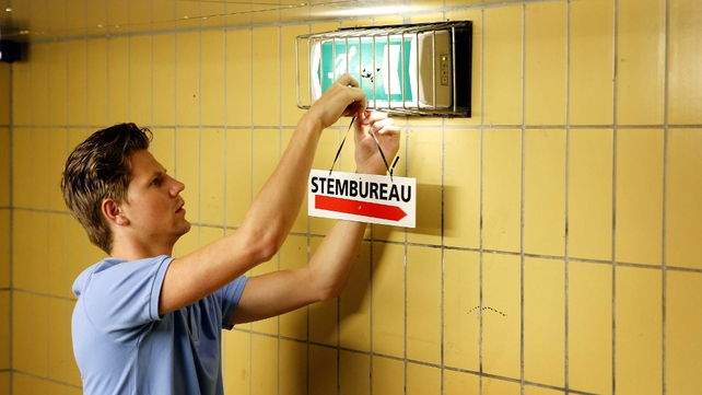 An employee places a board to point the way to the polling station at the train station of Castricum in the Netherlands