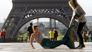 A model dressed as a mermaid prepares before posing in front of the Eiffel Tower during sunrise in Paris