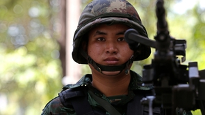 A Thai solider stands guard with a heavy machine gun