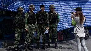 Thai soldiers pose for a photograph as they guard an area near government buildings in Bangkok