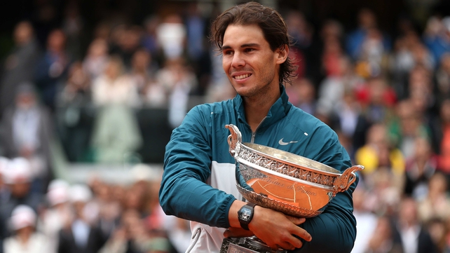 Rafael Nadal poses with the Coupe des Mousquetaires trophy after winning the 2013 French Open