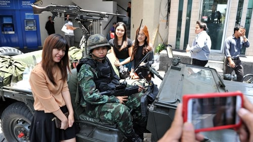 Passers by pose for a photo with Thai army soldiers standing guard on a city centre street