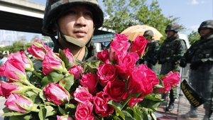 A Thai soldier holds flowers after receiving them from a small group supporting the army outside the Army Club in Bangkok