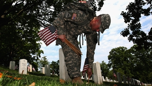 A US Army Captain places a flag at a grave site in Arlington National Cemetery as part of the 'Flags-In' ceremony