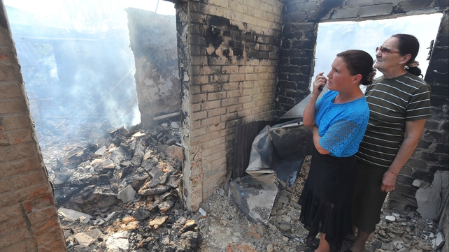 Local residents look at a house destroyed during fighting Ukrainian troops and pro-Russian militants in of Semenovka