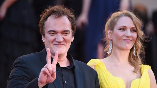 Tarantino makes the peace symbol to the crowd