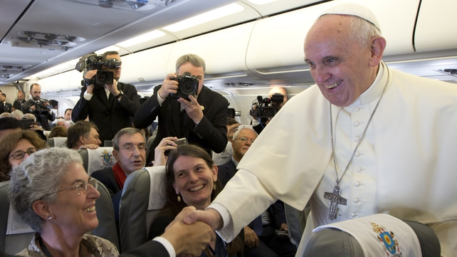 Francis greets journalists aboard the papal flight on his way to Amman