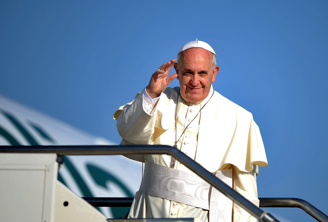 The pontiff waves before boarding the plane for his trip to the Holy Land