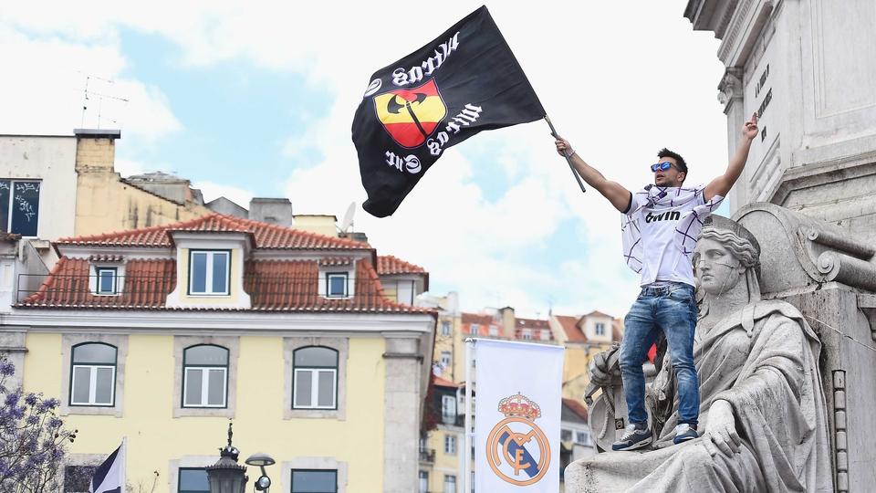 A Los Blancos fan is cradled by a statue in Lisbon