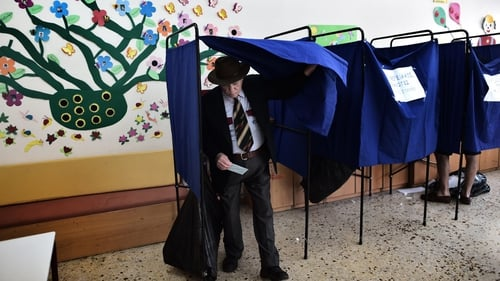 A man steps out of a polling booth after voting for the European Parliament elections at a polling station in Athens