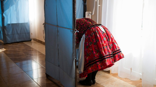 Wearing folk costume, a woman fills out her ballot in Ajak, northeast of Budapest, Hungary