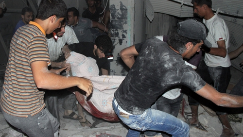 Men carry a body from a destroyed building after shelling during the night on the northern Syrian city of Aleppo
