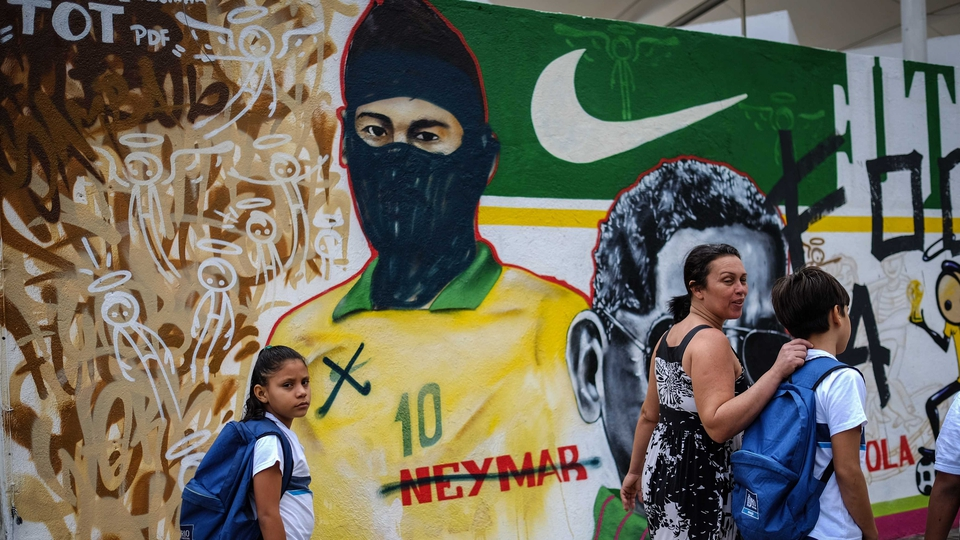People walk past graffiti depicting Brazilian national footballer Neymar with a hood used by members of the anarchist group known as Black Bloc