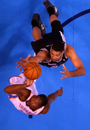 Tim Duncan of the San Antonio Spurs and Kevin Durant of the Oklahoma City Thunder go up for a loose ball in the first half during Game Four of Western Conference play-off