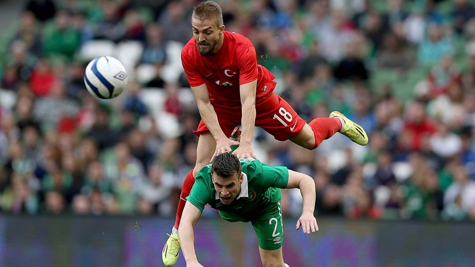 Seamus Coleman of Ireland is leap-frogged by Caner Erkin of Turkey
