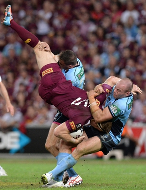 Brent Tate is picked up in the tackle by Josh Reynolds and Beau Scott during game one of the State of Origin series between the Queensland Maroons and the NSW Blues