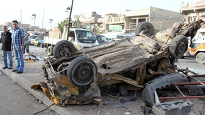 Iraqis inspect destruction in the street following an explosion the previous day in Sadr City, Baghdad
