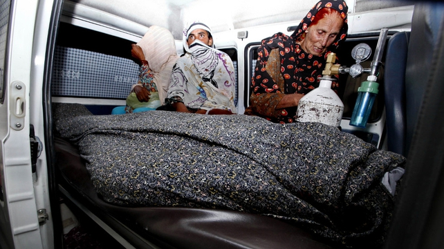 Relatives transport the body of Farzana Iqbal who was beaten to death on Tuesday