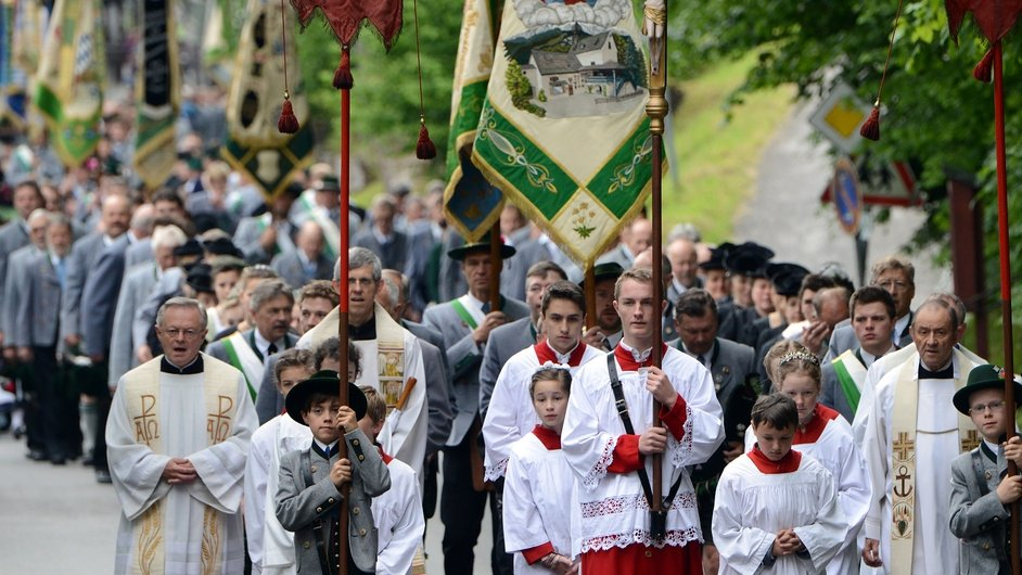Pilgrims in traditional Bavarian folk costumes march to an outdoor mass to celebrate Ascension at Birkenstein, Germany