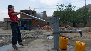 Afghan child collects water from a hand pump in Kabul as the Taliban wage an increasingly bloody insurgency against the government
