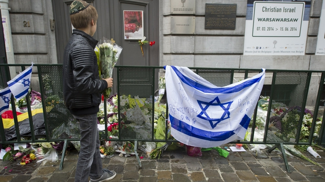 A Jewish boy stands with flowers in front of an Israeli flag in front of the Jewish Museum
