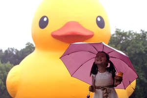 A girl posing for a photograph with an18-metre-tall Rubber Duck in eastern China's Zhejiang province