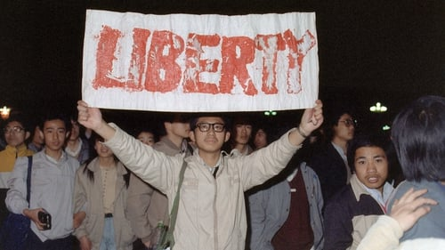 A student displays a banner with one of the slogans chanted by the crowd of some 200,000 pouring into Tiananmen Square 22 April 1989