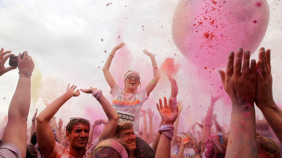 Runners celebrate in the Festival Area after The Colour Run in London, which is known as 'the happiest 5km on the planet'