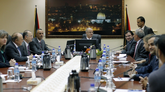 Palestinian Prime Minister, Rami Hamdallah (C) chairs the first cabinet meeting of the new Palestinian unity government in the West Bank city of Ramallah