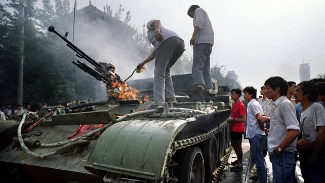 Chinese residents check a burning armoured personnel carrier which was set on fire by rioters fighting back when the army opened fire on the civilians