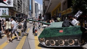 Activists push a replica of a Chinese tank across a street in Hong Kong to commemorate the 1989 military crackdown