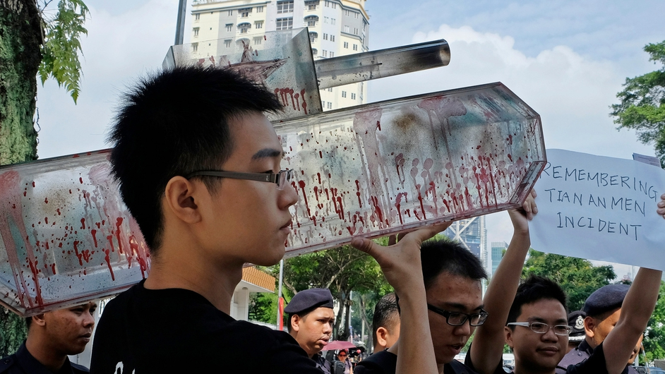 A protester holds a replica of a tank covered with red paint to symbolise blood during a protest in front of the Chinese Embassy in Kuala Lumpur, Malaysia